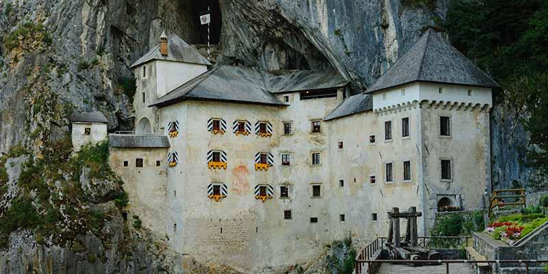 Het spectaculaire roofridderkasteel van Predjama in Slovenië ligt onder een overhangende rots geplakt